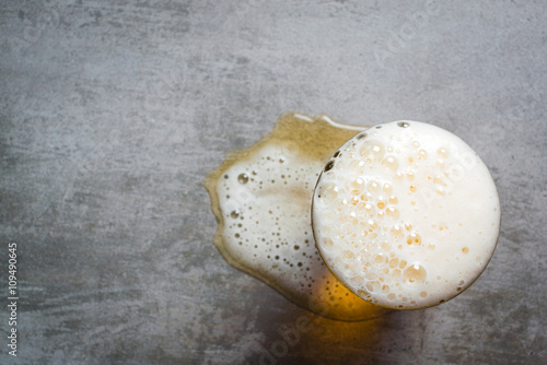 Fotografering  Glass of beer and a puddle of beer on the table