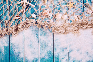 NaklejkaWooden blue background with sand, net and shells