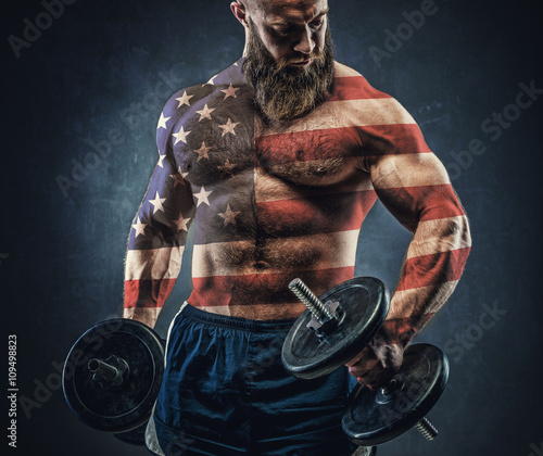 Photo  Power athletic bearded man in training pumping up muscles with d