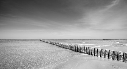 Panel Szklany PodświetlaneBlack and white panoramic photo of a wooden breakwater on a beach.