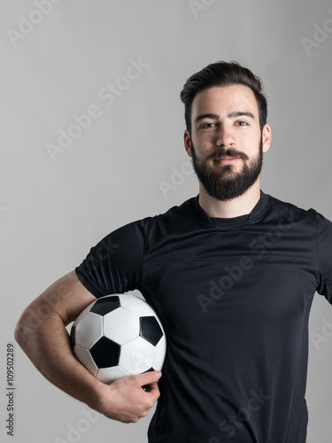 Friendly smiling bearded soccer player holding ball under his arm looking at camera over gray studio background.