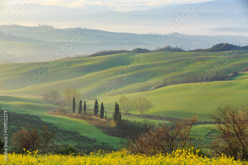Poster Kaki Misty sunrise in the Val d'Orcia, or Valdorcia, a region of Tuscany, central Italy, which extends from the hills south of Siena to Monte Amiata.