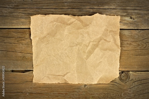 Fényképezés  Blank crumbled brown paper on a rustic wooden background