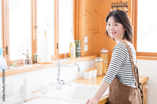 Photographie  attravtive asian woman in the kitchen