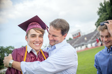 Young Man Being Hugged By Father At Graduation Ceremony