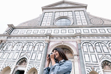 Low Angle View Of Young Woman Using Digital Camera In Front Of Church, Piazza Santa Maria Novella, Florence, Tuscany, Italy