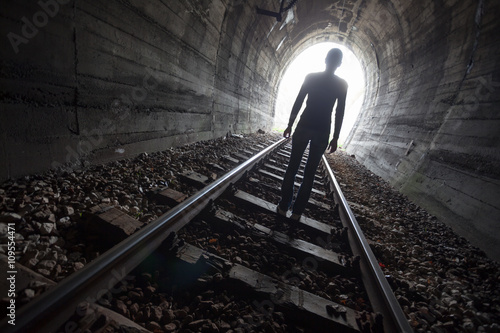 Photo Man in a tunnel looking towards the light