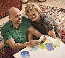 Male Couple Sitting On Floor Choosing Color Swatch