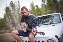 Young Man Playing Banjo On Jee...