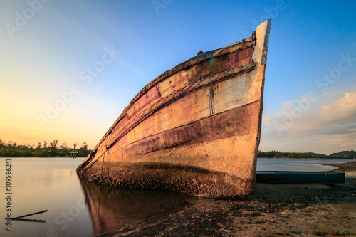 Foto op Canvas Schipbreuk Abandoned Ship during sunset moment at sabah borneo malaysia Image has grain or blurry or noise and soft focus when view at full resolution. (Shallow DOF, slight motion blur)