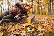 Young Couple Play Fighting With Autumn Leaves In Forest