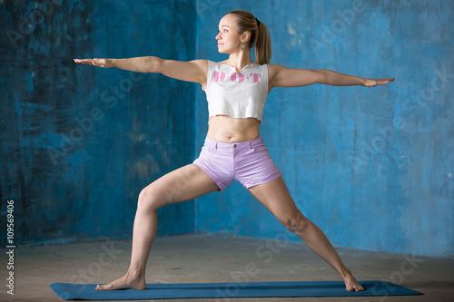 Beautiful sporty young woman Doing Warrior II posture