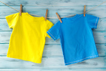 Two Bright Baby T-shirts Hanging On A Clothesline On A Blue Wooden Background