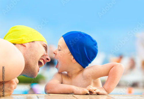 happy child and dad with swimming pool cap have fun in a pool Wallpaper Mural