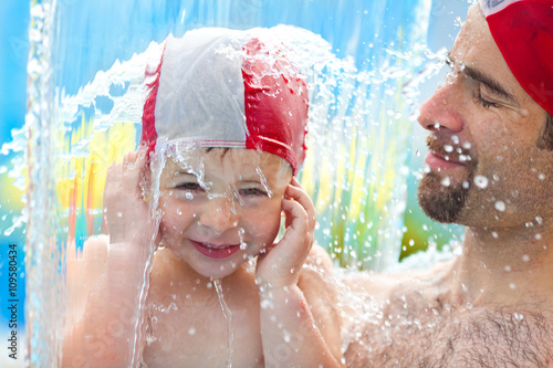 Photo  happy child and dad with swimming pool cap have fun in a pool