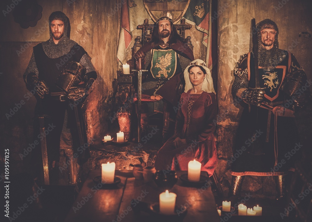 Fototapeta Medieval king with his queen and knights on guard in ancient castle interior.