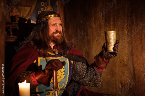 Fotografie, Obraz  Old medieval king with goblet of wine on the throne in ancient castle interior