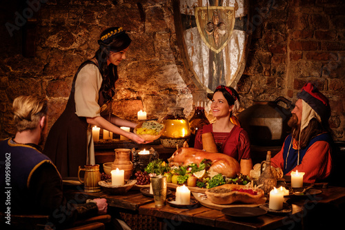 Cuadros en Lienzo Medieval people eat and drink in ancient castle kitchen interior