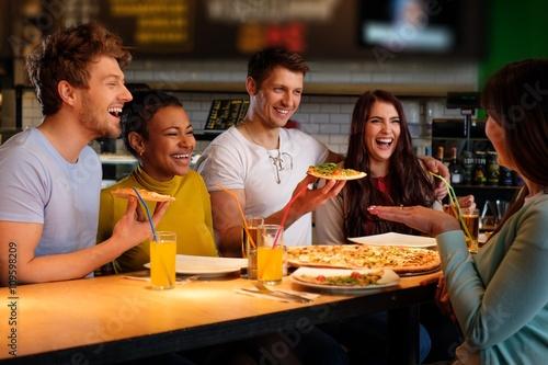 Foto op Canvas Pizzeria Cheerful multiracial friends having fun eating in pizzeria.