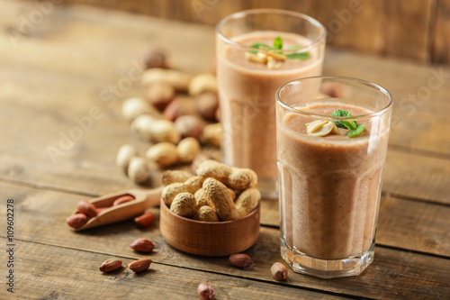 Photo  Fresh banana cocktail with peanuts on wooden table