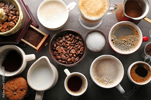 Fotografía  Different types of coffee in cups on dark table, top view