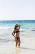 young beautiful girl in swimsuit bikini posing on beach, fashion model, fitness figure.