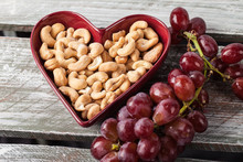 Cashews In A Heart Shaped Bowl With Red Seedless Grapes Angled View