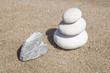 heart shaped stone and stack of pebbles on balance on sand