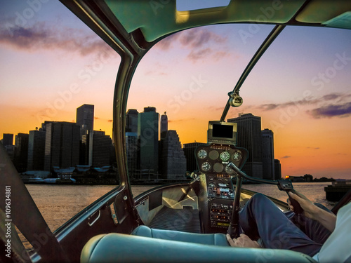 Photo  Helicopter cockpit on New York skyline at sunset, with pilot arm and control boa