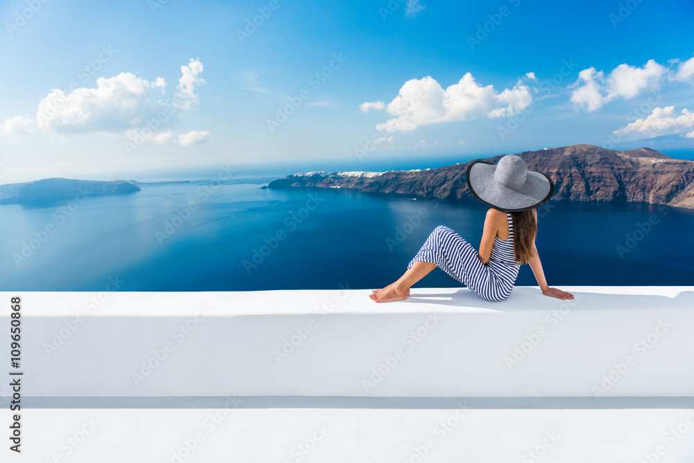 Fototapeta Europe Greece Santorini travel vacation. Woman looking at view on famous travel destination. Elegant young lady living fancy jetset lifestyle wearing dress on holidays. Amazing view of sea and Caldera