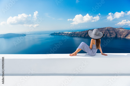 Fototapeta Europe Greece Santorini travel vacation. Woman looking at view on famous travel destination. Elegant young lady living fancy jetset lifestyle wearing dress on holidays. Amazing view of sea and Caldera obraz