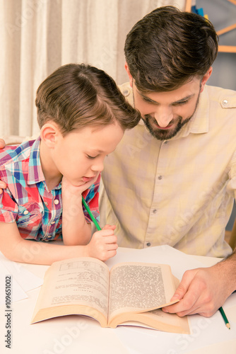 Photo  Close up portrait of handsome  father reading book to his son