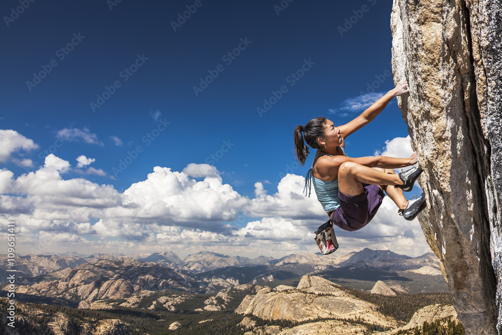 Fototapety, obrazy: Rock climber clinging to a cliff.