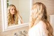 canvas print picture - Beautiful blonde looking at herself in the bathroom mirror