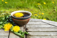 Tea From Dandelion  In A Rustic Earthenware Cup On A Wooden Table