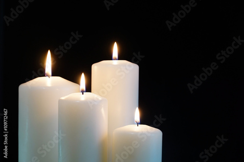 Fototapeta burning candles isolated on black background. obraz na płótnie