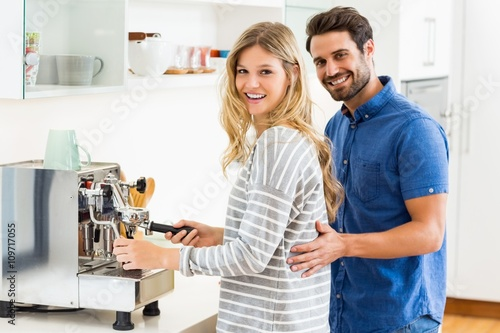 Leinwand Poster Young couple preparing coffee from coffeemaker
