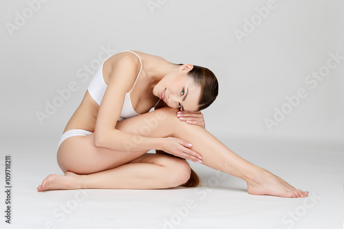 Obraz Slim tanned woman's body over gray background - fototapety do salonu
