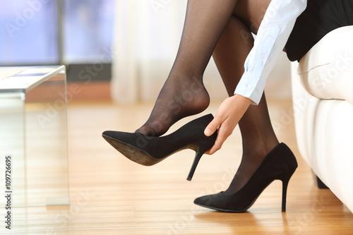 Fotografia  Businesswoman taking off shoes