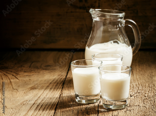Goat milk in glasses, vintage wooden background, selective focus