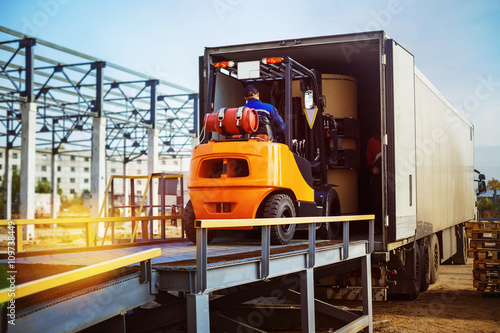 Zdjęcie XXL Wózek widłowy przenosi ładunek z magazynu na ciężarówkę na zewnątrz