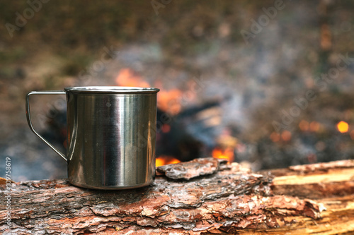 Poster Camping Iron cup with hot tea stands on a log near the fire. Journey into the wild concept.