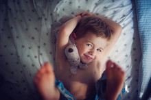 Smiling Boy Lying On Bed With Cuddly Toy