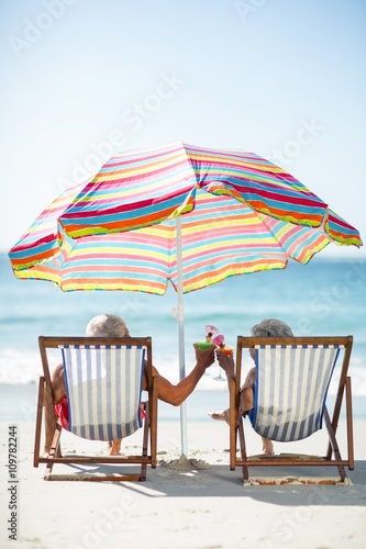 Cute mature couple lying on deckchairs Canvas Print