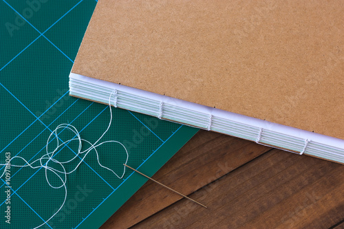 Fotografia, Obraz  Handbound book with needle and thread