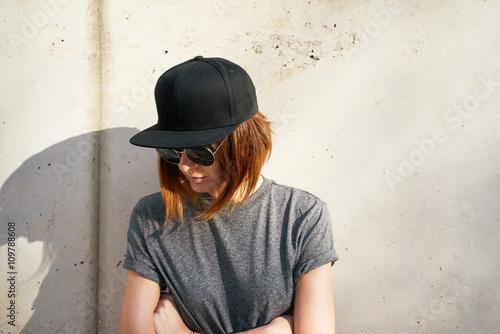 Stampa su Tela  Female model wearing a black blank cap and sunglasses looking away