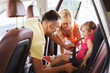 happy parents fastening child with car seat belt