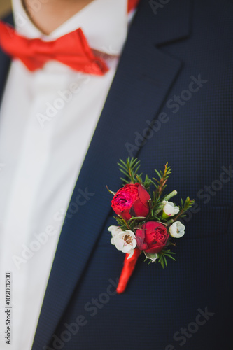 Photographie Close up of white and red rose corsage on man suit