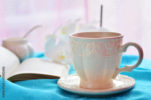 Fotografie, Tablou  A cup of coffee, open book and flowers on a blue tablecloth