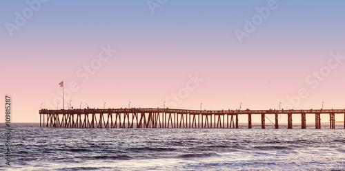 fototapeta na lodówkę Vintage toned long wooden pier at sunset.